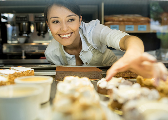 Woman reaching into refrigerated case for pastries